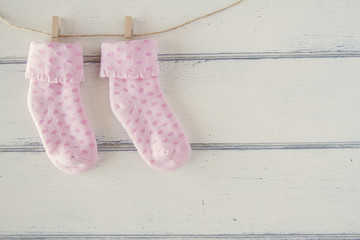 Pink socks for baby girl hanging on rope with clothespins