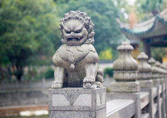 stone lion sculpture on the fence in the park