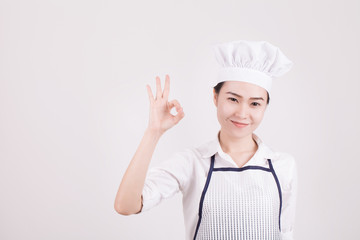 Closeup portrait of a smiling female cook gesturing okay sign