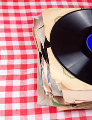 Pack of retro vinyl records on a vichy tablecloth
