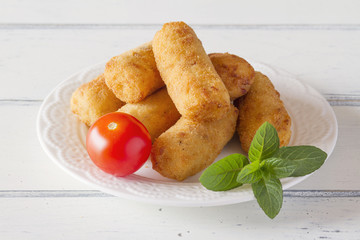 Some croquettes with tomato and lettuce
