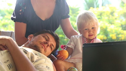 small blonde baby girl and her father mother watching cartoon