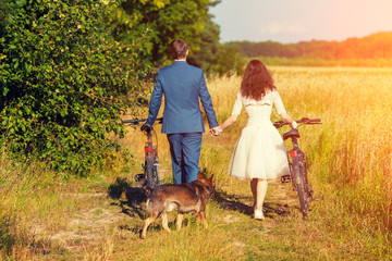 Young happy bride and groom carry bikes in the wheat field