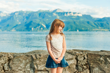 Adorable little girl resting by the lake