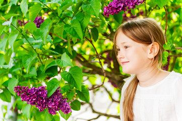 Outdoor portrait of a cute little girl against beautiful lilac