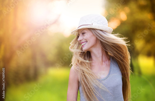 Beautiful woman outside in a park. - 76895615