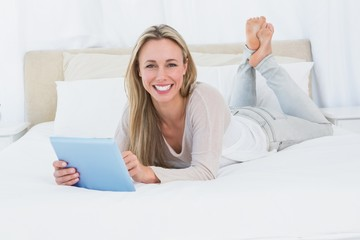 Cheerful blonde using tablet pc on the bed