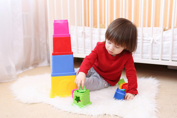 little boy playing with educational toy at home