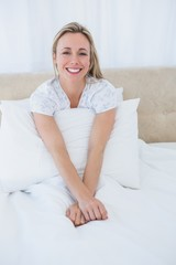 Smiling blonde relaxing in bed