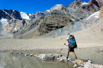 Man with backpack resting on trekking pole moves a river