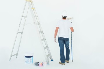 Man with paint roller standing by ladder