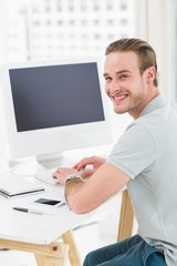 Smiling businessman sitting at desk typing on keyboard
