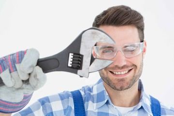 Confident repairman wearing protective glasses holding wrench