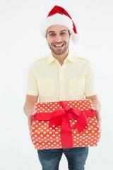 Smiling man wearing Santa hat while holding gift