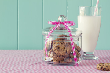 Glass jar with chocolate chip cookies. A glass of milk. Vintage
