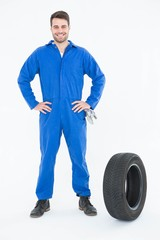 Smiling mechanic with hands on hips standing by tire