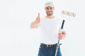 Happy man with paint roller gesturing thumbs up