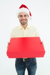 Happy man wearing Santa hat while holding red gift