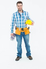 Confident handyman holding hard hat and gloves