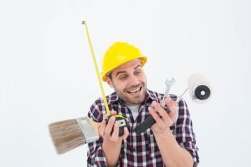 Happy repairman holding various tools