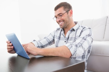 A smiling man using a tablet
