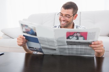 A smiling man reading a newspaper