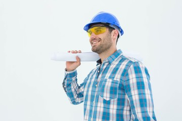 Smiling architect looking away while holding blueprint