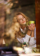 Dreamy woman with a cup of coffee in cafe, enjoying the aroma