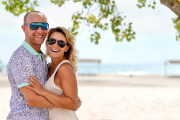 Portrait of happy beautiful couple standing at the sunny beach.