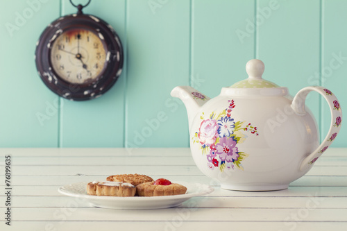 Fotobehang Thee A teapot, german cookies and a clock. Tea time. Vintage