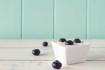 Some blueberries on a bowl with greek yogurt. Vintage