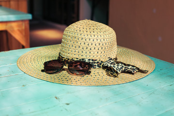 Straw hat and sunglasses on table