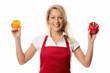 Frau mit Schürze präsentiert Paprikaschoten