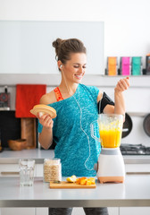 Happy fitness young woman making pumpkin smoothie in kitchen
