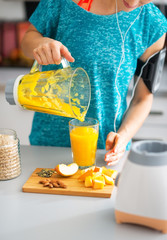 Close-up on fitness woman pouring pumpkin smoothie in glass