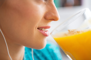 Close-up on fitness young woman drinking pumpkin smoothie