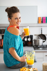 Portrait of happy fitness woman with glass of pumpkin smoothie