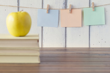 An apple, three sheets of paper on clothespins. Three books.