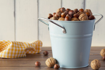 Walnuts and hazelnuts in shells on a turquoise bucket.