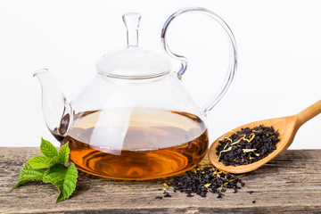 Glass Kettle of Tea with mint leaf on wooden Background