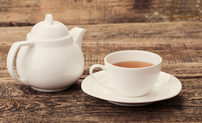 Image of ivory tea cup and kettle on wooden palette