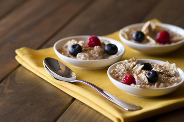 Three white bowls with cereals, raspberries and blueberries.