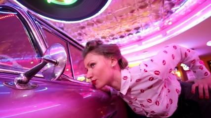 Beautiful pinup girl checking makeup in a car mirror.