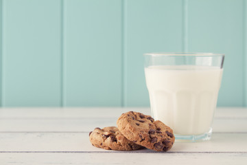 Chocolate chip cookies and a glass of milk with a straw. Vintage