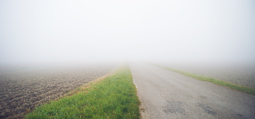 Country road in autumn with fog