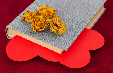 Four dried yellow roses lying on the book with two red hearts