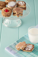 Cookies on a cake stand and a glass of milk. Vintage look.