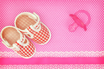 Baby shoes and pink pacifier on polka dots background
