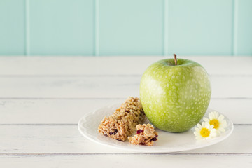A apple on a plate with honey cereals bar. Vintage