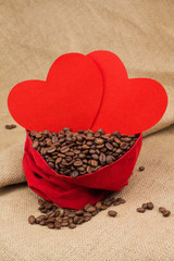 Coffe beans in red velvet sac with two red hearts